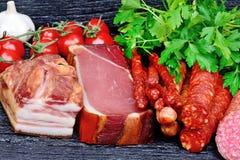 Salsiccie con i pomodori ciliegia, il prezzemolo e l'aglio sulla tavola Immagini Stock Libere da Diritti