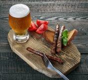 Salsiccie con i pomodori e la birra Immagini Stock