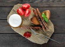 Salsiccie con i pomodori e la birra, vista superiore Immagini Stock Libere da Diritti