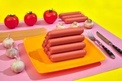 Salsiccie con i pomodori, gli spaghetti e l'aglio su un fondo minimo giallo e rosa Disposizione piana Vista superiore Immagini Stock
