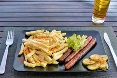 Salsiccie con le patate fritte sulla banda nera Immagini Stock