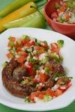 Salsiccie cotte con salsa di verdure Immagini Stock
