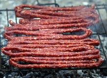 Salsiccie del bastone su una griglia Immagini Stock