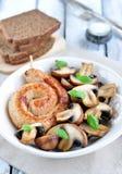 Salsiccie del pollo con i funghi arrostiti e basilico su una tavola di legno bianca Fotografia Stock
