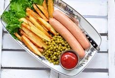 Salsiccie del pollo con la patata fritta, il ketchup e la lattuga fresca Immagine Stock Libera da Diritti