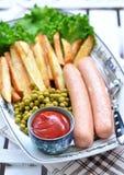 Salsiccie del pollo con la patata fritta, il ketchup e la lattuga fresca Fotografia Stock