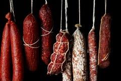 Salsiccie deliziose che appendono sul fondo fotografia stock