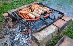 Salsiccie deliziose su una griglia del metallo che griglia sopra i carboni caldi Immagini Stock