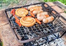 Salsiccie deliziose su una griglia del metallo che griglia sopra i carboni caldi Immagine Stock Libera da Diritti