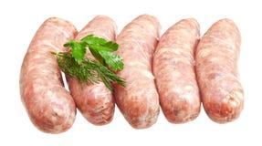 Salsiccie della carne cruda con i verdi Immagini Stock