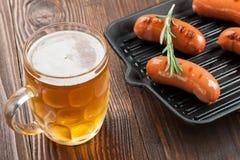 Salsiccie e birra cotte Immagini Stock