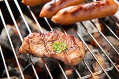 Salsiccie e carne del BBQ sulla griglia Fotografia Stock