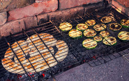 Salsiccie e zucchini che cucinano su una griglia Fotografia Stock Libera da Diritti