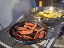 Salsiccie ed uova fritte che sono fornello di campeggio semplice pronto del onb all'aperto con il sole che splende su  Immagine Stock