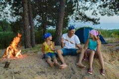 Salsiccie felici di torrefazione della famiglia sopra fuoco di accampamento concetto di turismo e di campeggio fotografie stock libere da diritti
