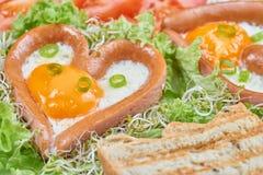 Salsiccie a forma di del cuore con le uova fritte Fotografia Stock Libera da Diritti