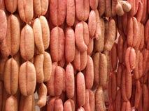Salsiccie fresche che appendono sugli ami Fotografia Stock