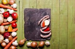 Salsiccie fresche su fondo di legno verde Salsiccie, verdure Fotografia Stock