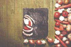 Salsiccie fresche su fondo di legno verde Salsiccie, verdure Fotografia Stock Libera da Diritti