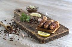Salsiccie fritte con bacon su un bordo di legno Fotografia Stock Libera da Diritti