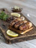 Salsiccie fritte con bacon su un bordo di legno Immagine Stock