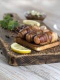 Salsiccie fritte con bacon su un bordo di legno Immagini Stock Libere da Diritti