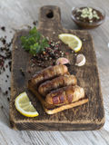 Salsiccie fritte con bacon su un bordo di legno Immagini Stock