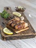 Salsiccie fritte con bacon su un bordo di legno Immagine Stock Libera da Diritti