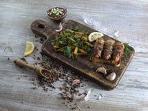 Salsiccie fritte con bacon su un bordo di legno Fotografie Stock