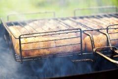 Salsiccie fritte su una griglia della griglia Fotografia Stock