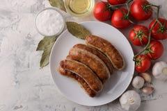Salsiccie grigliate con i pomodori, l'olio di girasole e l'aglio su un fondo leggero Vista superiore immagini stock