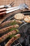Salsiccie o bratwurst di Norimberga con le patate ed i rosmarini sulla griglia Fotografie Stock