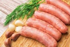 Salsiccie per la frittura, aglio, aneto con un tagliere di legno Fotografie Stock