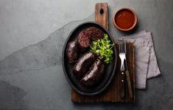 Salsiccie sanguinose - preta cileno sul piatto del ferro, vista superiore, fondo grigio dell'ardesia immagine stock libera da diritti