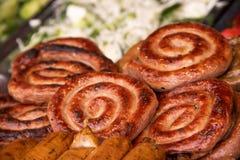 Salsiccie a spirale arrostite su un piatto di pianta e delle verdure nei precedenti fotografie stock libere da diritti
