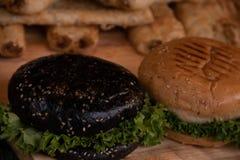 Salsiccie a spirale arrostite su un piatto di pianta e delle verdure nei precedenti fotografia stock