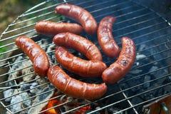 Salsiccie su una griglia del barbecue Immagine Stock
