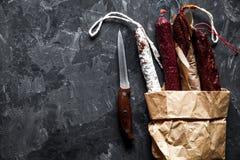 Salsiccie su una struttura di carta su un fondo scuro con pepe Fotografia Stock