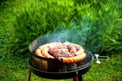 Salsiccie sul gril di fumo immagine stock