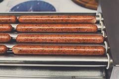 Salsiccie sulla macchina del professionista per la preparazione del hot dog Fotografia Stock