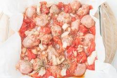 Salsiccie tagliate crude nel piatto di cottura Immagine Stock Libera da Diritti