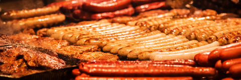 Salsiccie tedesche Il processo di cottura sopra un fuoco Fotografia Stock Libera da Diritti