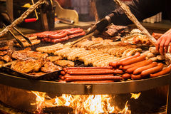 Salsiccie tedesche Il processo di cottura sopra un fuoco Immagine Stock Libera da Diritti