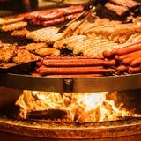 Salsiccie tedesche Il processo di cottura sopra un fuoco Fotografie Stock
