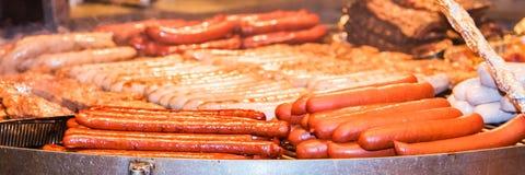 Salsiccie tedesche Il processo di cottura sopra un fuoco Immagini Stock