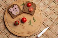 Salsicha com pão preto e tomate para o almoço, pão preto com o tomate no fundo de madeira imagem de stock