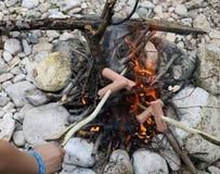 A salsicha cozinhou no fogo durante o acampamento de verão do boyscout imagens de stock royalty free