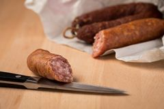 Salsicha de carne de porco de Ring Salami com o Bierbeißer alemão no papel de cera com a faca no fundo da placa de madeira para  foto de stock royalty free