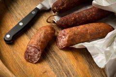 Salsicha de carne de porco de Ring Salami com o Bierbeißer alemão no papel de cera com a faca no fundo da placa de madeira para  fotos de stock royalty free