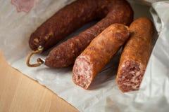 Salsicha de carne de porco de Ring Salami com o Bierbeißer alemão no papel de cera no fundo da placa de madeira para o jantar de imagens de stock royalty free